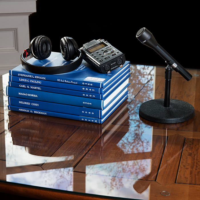 Oral History - stack of books and microphone on table