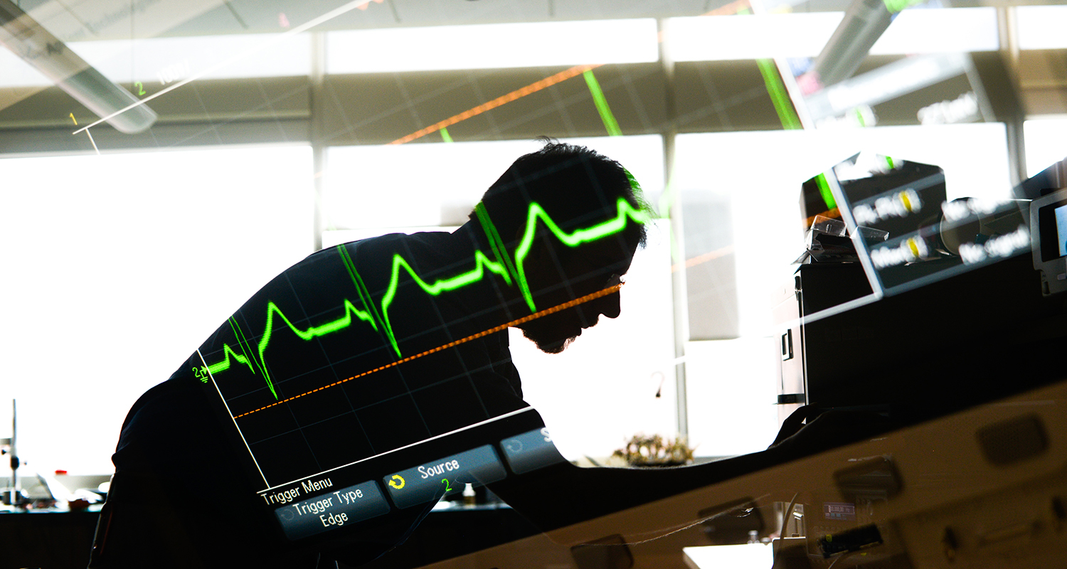 Researcher bent over a lab table with image of heart monitor superimposed.