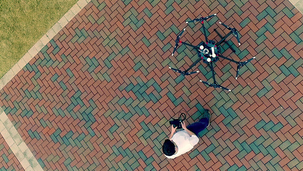 Shot from above, a man stands with a grounded drone.