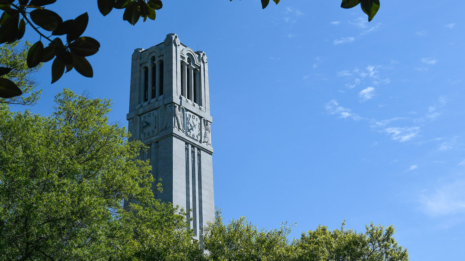 The NC State belltower, framed against a clear sky.