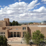 The University of New Mexico's campus against a blue sky.